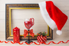 Christmas ornaments on wooden background. Glass, candle, gift, hat Santa Claus. stock images
