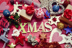 Christmas ornaments and word xmas. High-angle shot of some letters forming the word xmas on a red rustic wooden surface surrounded by a pile of gifts and Royalty Free Stock Photography
