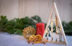 Christmas ornaments with snow, pine tree and xmas lights. Christmas ornaments with xmas lights and dry fruits over a snowy floor with pine tree and wood Stock Images