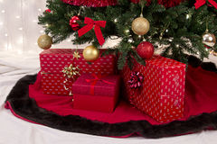 Christmas packages under the tree. Three wrapped Gifts under a Christmas tree Stock Photo