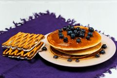 Christmas pancakes with honey and blueberries on a violet napkin. Breakfast for children with pancakes, honey and blueberries. Christmas pancakes with honey and Stock Image
