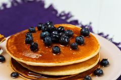 Christmas pancakes with honey and blueberries on a violet napkin. Breakfast for children with pancakes, honey and blueberries. Christmas pancakes with honey and Stock Photo