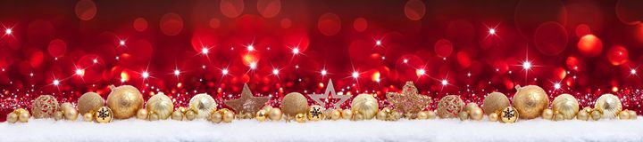 Christmas panorama border with golden decorations. Golden christmas decoration panorama on red bokeh background royalty free stock image