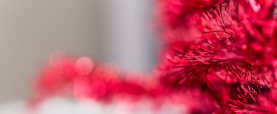 Christmas panorama with red tinsel in the foreground and blured background. Christmas panorama with red glitter in the foreground and blured background with copy stock images