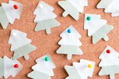 Christmas paper tree reminder on cork board abstract background Stock Photos