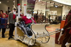 Christmas parade at the mall. Santa sitting in a white sled with his helper. Open stores are bright and decorated stock photography