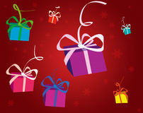 Christmas Parcels. Red parcels falling, snowflakes faded in background Royalty Free Stock Image