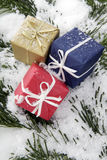 Christmas parcels on snow-covered fir branch, close up Royalty Free Stock Photos
