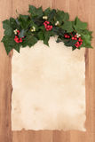 Christmas Parchment Letter. Christmas parchment blank letter with border of holly, ivy and mistletoe over oak background Stock Photography