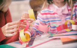 Christmas: Parent and Child Work On Paper Chain Garland stock images