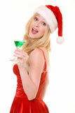 Christmas Party. Attractive blond caucasian woman wearing red and white Christmas dress and santa hat holding on to a green martini drink on white royalty free stock image