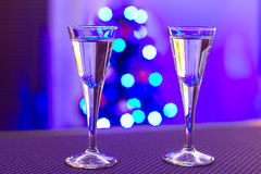 Christmas party. Two glasses of vodka with blurry christmas tree background Stock Image