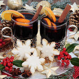 Christmas Party Food and Drink. With mulled wine, gingerbread biscuits, with gold bauble decorations, spices, fruit, holly and snow covered fir stock images