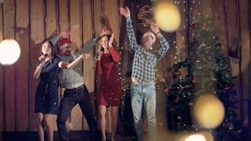 Two women sing and dance with two men at Christmas Eve. stock video