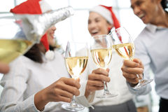 Christmas party in full swing. Close-up image of colleagues clinking glasses at Christmas party Royalty Free Stock Images
