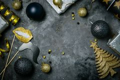 Christmas party invitation - silver, gold and black decorations. Top view Royalty Free Stock Image