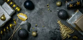 Christmas party invitation - silver, gold and black decorations. Top view stock photos