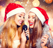 Christmas party, karaoke. Beauty girls in santa hats singing Stock Image