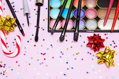 Christmas party makeup. Bright color glitter eyeshadow, mascara, eyeliner, red lipstick, lip liners, brushes and applicator with candy cane, gift wrap bows and royalty free stock photos