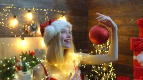 Christmas party. Sexy blonde woman holding red Christmas ball on Christmas tree backgroung. Christmas decorations. New stock footage