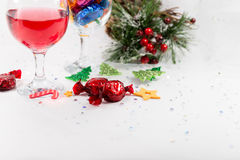Christmas party table decorations with wine, sweets and copy spa. Close up of Christmas party table decorations with wine and wrapped chocolate candy sweets stock photo