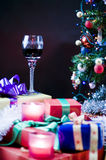 Christmas party table setting. With glass wine goblet, lit candles, gifts and decorated tree Stock Photography