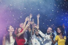 Group of young people celebrating new year with champagne at night club royalty free stock photography