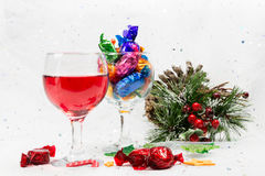 Christmas party treats of wine and wrapped chocolate candy sweet. S. Treats to enjoy the merry holiday season.on a snowy white background Royalty Free Stock Image