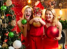Christmas party. Women red dresses festive mood celebrate christmas with little cute baby. Family bonds. Love peace joy. Wishes. Kid boy with mom or aunts royalty free stock photography