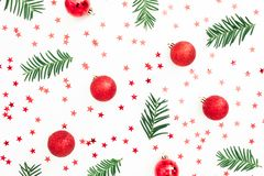 Christmas pattern of fir branches and red balls decoration with confetti on white background. Festive background. Flat lay, top vi stock photo