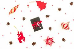 Christmas pattern. Christmas gift box, red toys and glittering confetti on white background. Flat lay, top view. Christmas pattern. Christmas gift box, red toys stock photo