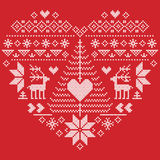 Christmas pattern in heart shape with reindeer, Christmas tree on red  background. Heart Shape Scandinavian Printed Textile  style and inspired by  Norwegian Royalty Free Stock Photography