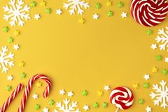 Christmas pattern with Lollipops sweets round copy space. Candy with snowflake, flat lay on yellow pastel background. Sweet sucker, candy, isolated minimal royalty free stock photography