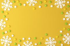 Christmas pattern with Lollipops sweets round copy space. Candy with snowflake, flat lay on yellow pastel background. Sweet sucker, candy, isolated minimal stock photo