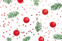 Christmas pattern made of fir branches and red balls decoration with confetti on white background. Festive background. Flat lay, t stock images
