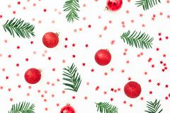 Christmas pattern made of fir branches and red decoration with confetti on white background. Festive background. Flat lay, top vie royalty free stock photography