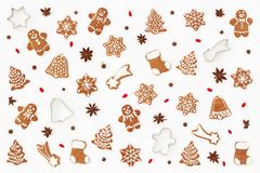 Christmas pattern made of gingerbread cookies, stars anise, baking molds and barberries on white background. Christmas and winter. Mood concept. Flat lay Stock Photos