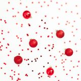 Christmas pattern made of red balls decoration with confetti on white background. Festive background. Flat lay, top view royalty free stock photography
