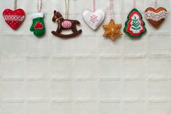 Christmas background with handmade felt decorations: hearts, star, rocking horse, gloves, gingerbreads. royalty free stock photos