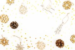 Christmas pattern with wooden tree decoration, snowflakes and pine cones on white. Flat lay, top view. Winter festive frame concep stock photography