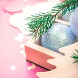 Christmas pearl decoration balls pink background. New Year Christmas Xmas holiday celebration composition pearl decorative toy ball wooden box fir branch stock images