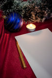 Christmas. Pen, paper, candle and blue ball. Royalty Free Stock Photography