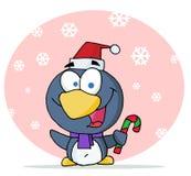 Christmas penguin holding a candy cane Stock Photos