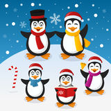 Christmas Penguins Family on the Snow. A funny cartoon Christmas family with five penguins, in a snowy scene. Eps file available Royalty Free Stock Photography