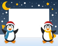 Christmas Penguins Horizontal Frame. Christmas horizontal photo frame with two cute cartoon penguin characters smiling and greeting on the snow. Eps file Stock Photo