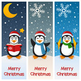 Christmas Penguins Vertical Banners. A collection of three vertical banners wishing a merry Christmas, with cute penguin characters on the snow. Eps file Stock Photography