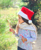 Christmas and people concept - child in santa hat with sweet lollipop cane and tree Royalty Free Stock Images