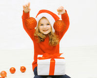 Christmas and people concept - happy little girl in winter hat Stock Photography