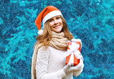 Christmas and people concept - happy pretty woman in red hat Royalty Free Stock Images