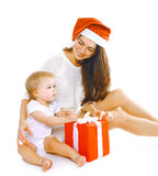 Christmas and people concept - happy smiling mother in santa hat Stock Images